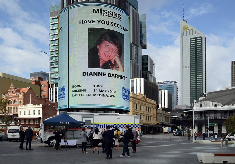 A large screen displays and image of a missing woman.