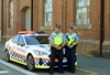 Two police officers stand in front of a police car smiling at the camera