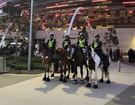 Four police officers on horses smile at the camera