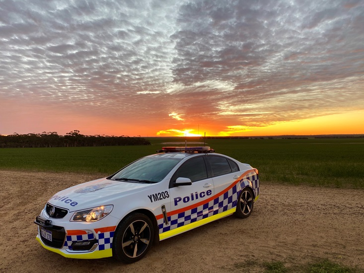 A police car with sunset behind